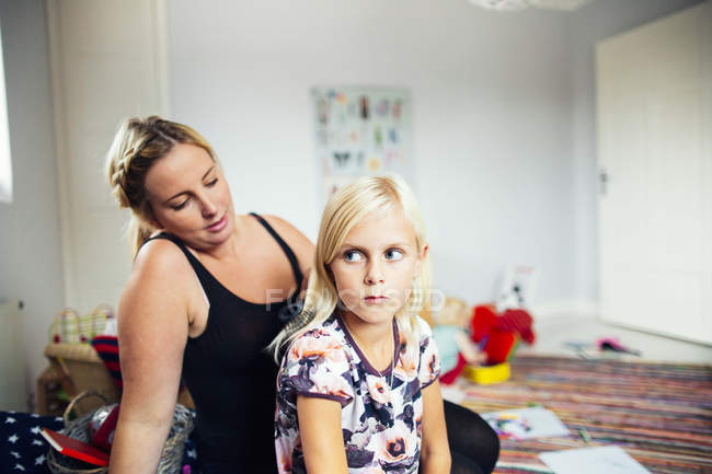 Mother making daughters hair at home — Stock Photo