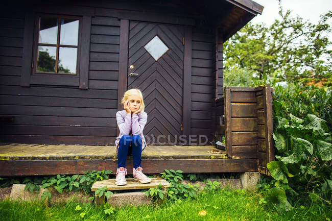 Sad girl sitting on porch — Stock Photo