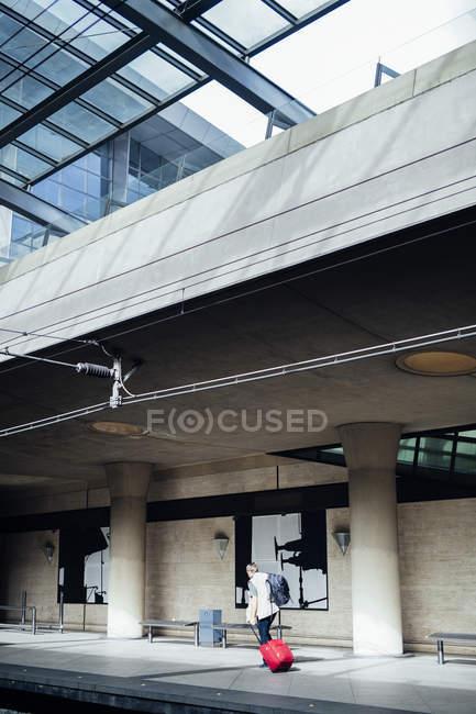 Uomo con bagagli a piedi sulla stazione ferroviaria — Foto stock