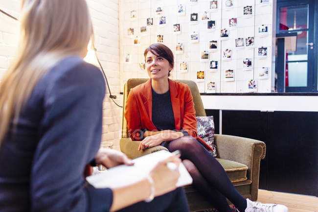Businesswoman talking to female colleague — Stock Photo