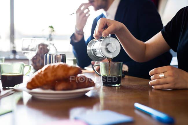Businesswoman poring coffee — Stock Photo