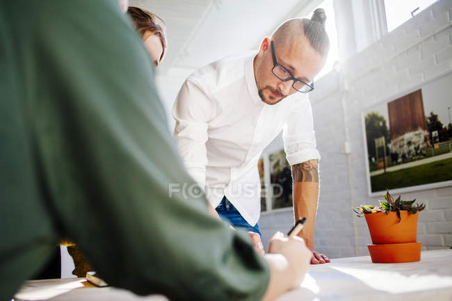Mid adult businessman with colleagues — Stock Photo
