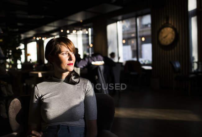 Frau sitzt im café — Stockfoto