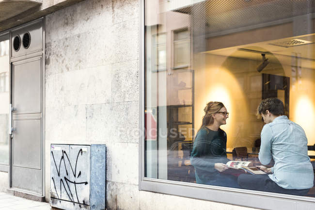 Businessman and businesswoman seen through glass — Stock Photo