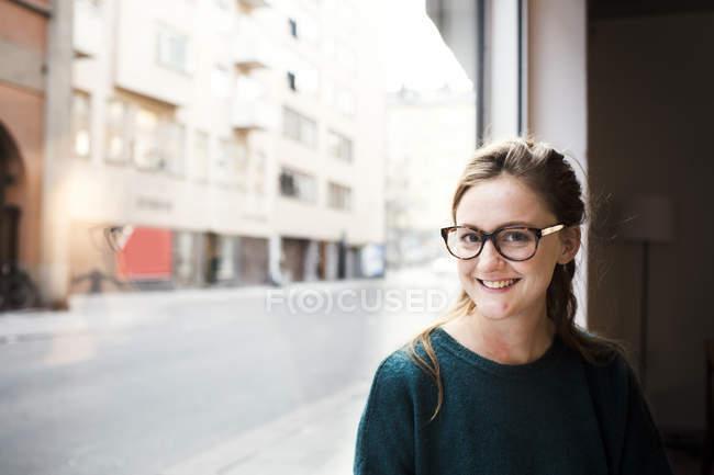 Milieu adulte femme d'affaires souriant par le bureau — Photo de stock