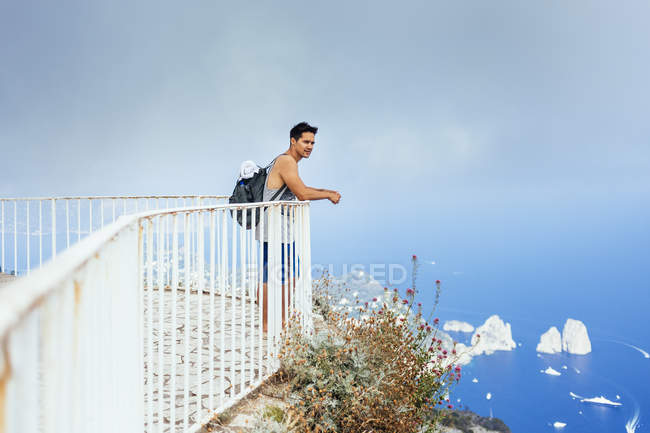 Young man standing by railing — Stock Photo