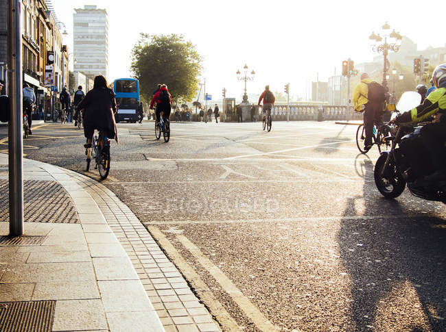 People riding bicycles on city street — Stock Photo