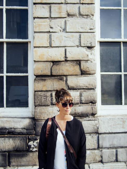 Модний жінка, стоячи проти стіни — стокове фото