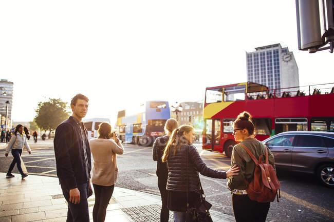 Friends standing on sidewalk — Stock Photo