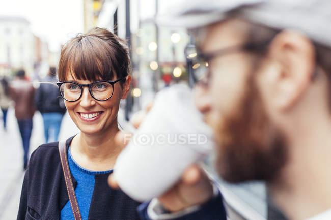 Mujer de pie con amigo - foto de stock