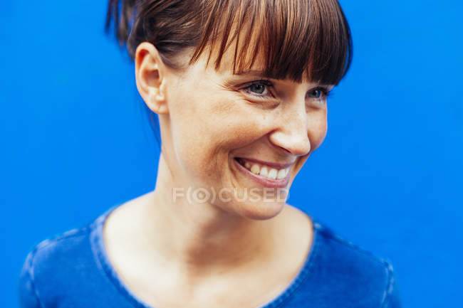 Happy woman against blue — Stock Photo