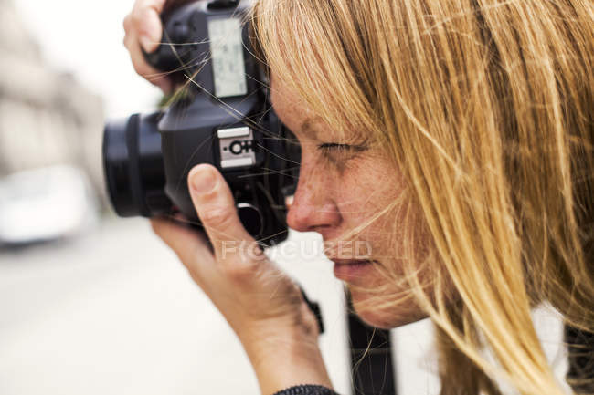 Woman photographing through digital camera — Stock Photo