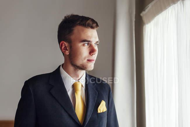 Hombre de negocios mirando hacia otro lado en la habitación del hotel - foto de stock