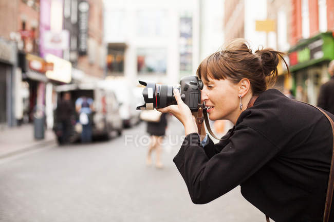 Woman photographing on city street — Stock Photo