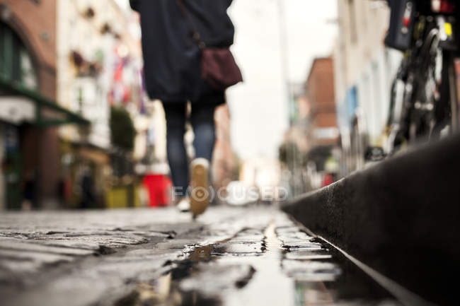 Person walking on wet footpath — Stock Photo