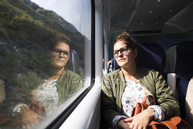 Бізнес-леді дивлячись через вікно поїзд — стокове фото