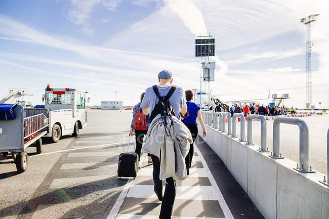 Amigos que se deslocam em direcção ao avião — Fotografia de Stock