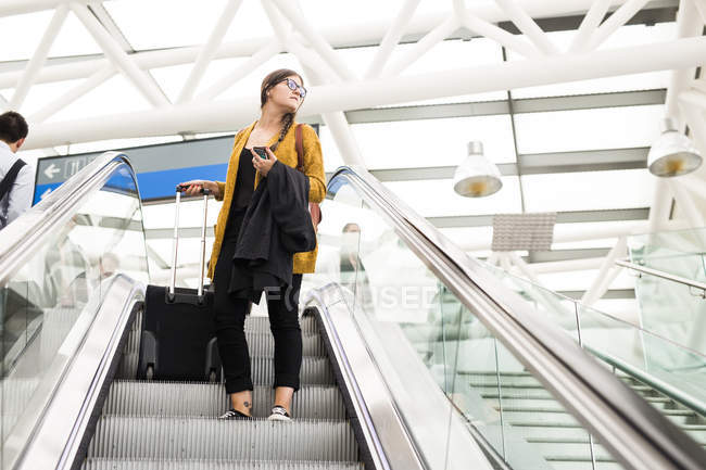 Businesswoman with luggage on escalator — Stock Photo