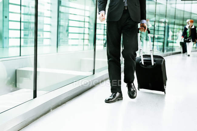 Businessman walking with luggage at airport — Stock Photo