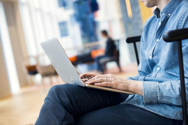 Geschäftsmann benutzt Laptop in Hotellobby — Stockfoto