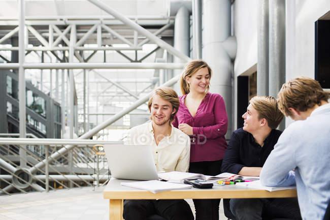 Друзья смотрят на человека с помощью ноутбука — стоковое фото