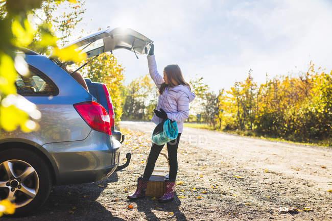 Ragazza guardando nel bagagliaio auto aperta — Foto stock