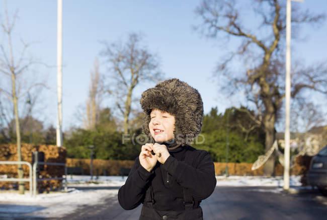 Ragazzo che indossa cappello di pelliccia sulla strada — Foto stock