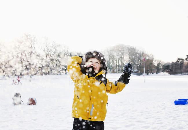 Glücklicher Junge genießt Schneefall — Stockfoto