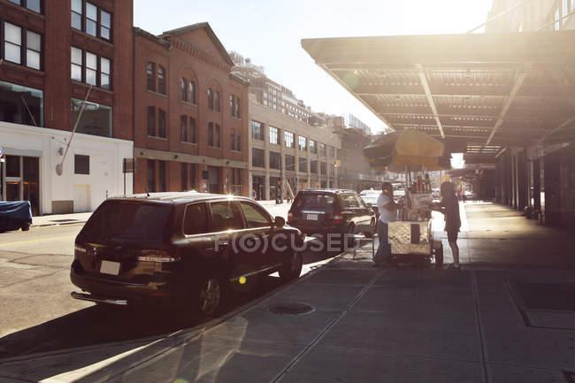 Автомобили на городской улице в солнечный день — стоковое фото
