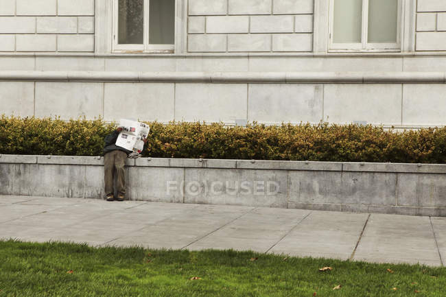 Man reading newspaper by building — Stock Photo