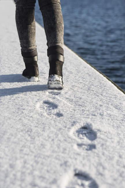 Mulher andando na calçada coberta de neve — Fotografia de Stock