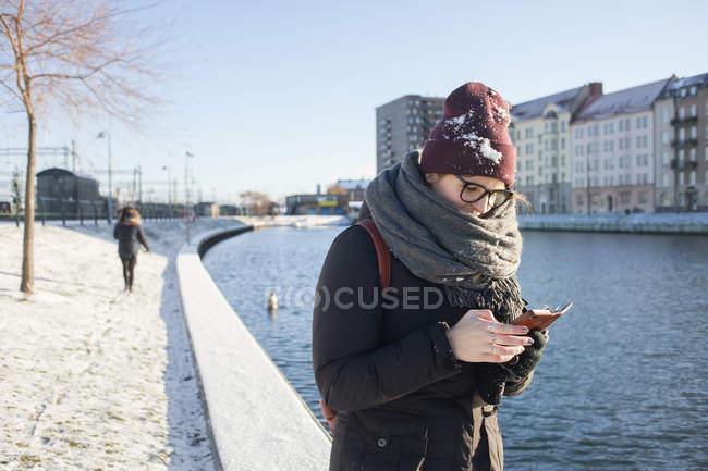 Mulher usando smartphone por canal — Fotografia de Stock