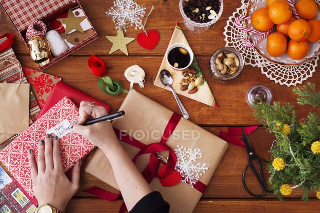 Hands writing on Christmas gift tag — Stock Photo