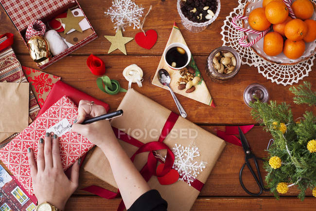 Hands writing on Christmas gift tag — Stock Photo