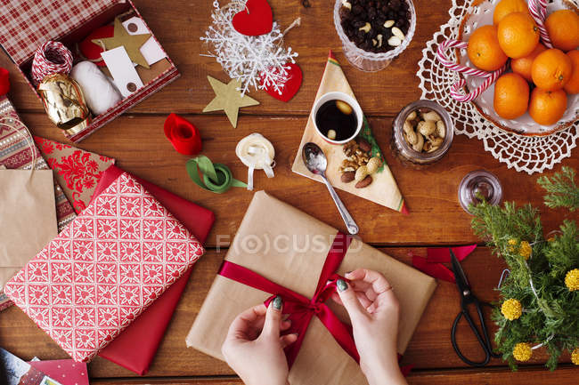 Mains lier bow sur le cadeau de Noël — Photo de stock