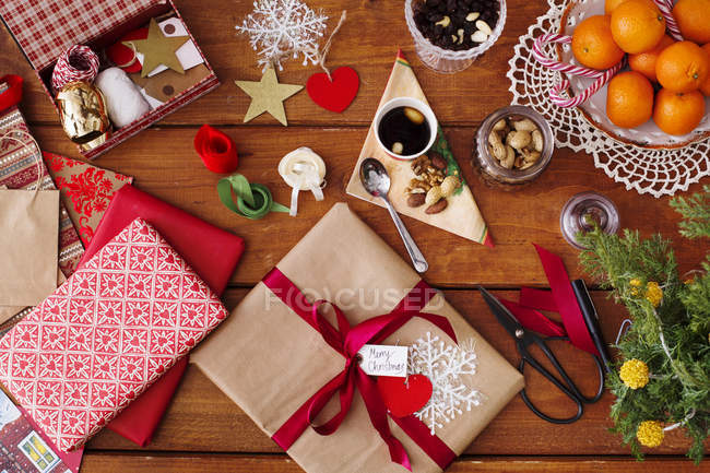 Christmas gifts with decorations and food on table — Stock Photo