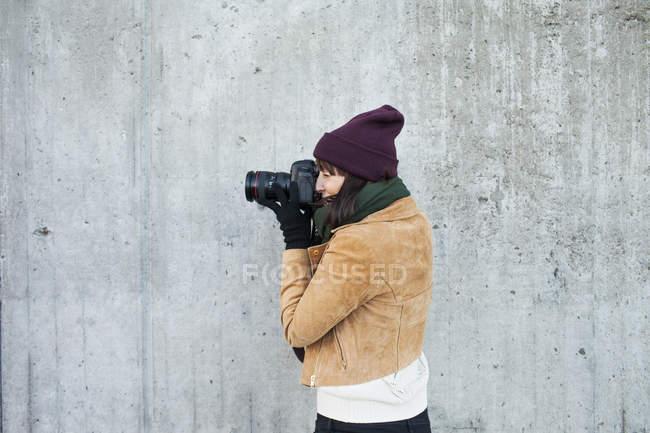 Женщина фотографирует у стены — стоковое фото