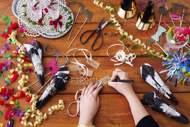 Hände auf Weihnachten Geschenkanhänger zu schreiben — Stockfoto