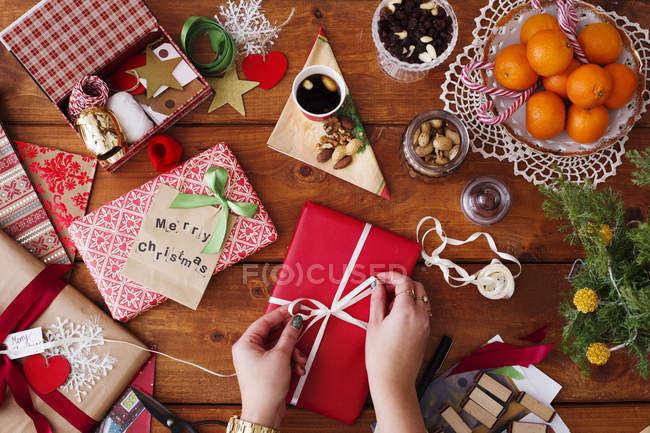 Mains attacher le ruban sur le cadeau de Noël — Photo de stock