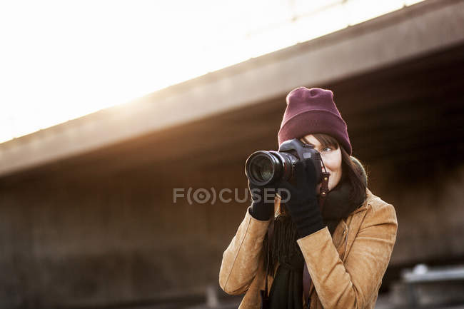 Woman photographing with camera outdoors — Stock Photo