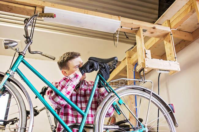 Repairman fixing bicycle seat — Stock Photo