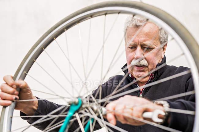 Senior woman Verschärfung Fahrradreifen — Stockfoto