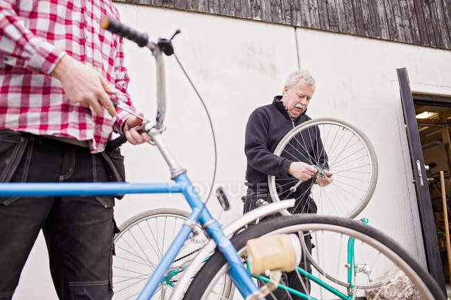Father and son repairing bicycles — Stock Photo