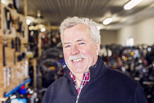 Enior proprietario nel negozio di biciclette — Foto stock
