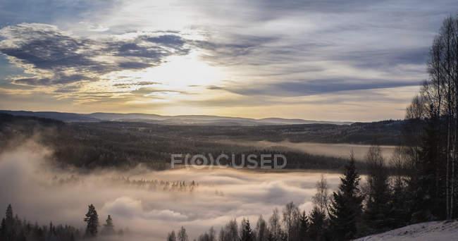 Paisaje y la niebla contra el cielo durante la puesta de sol - foto de stock