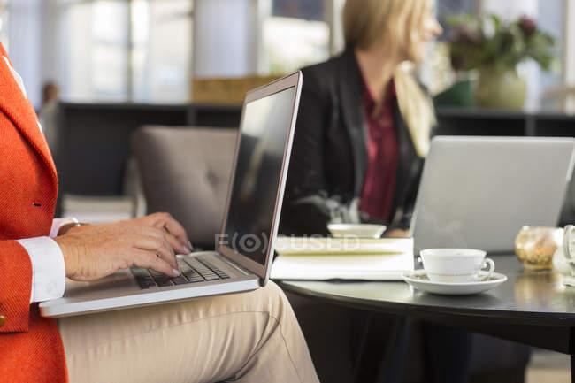 Geschäftsfrau benutzt Laptop bei Treffen im Restaurant — Stockfoto
