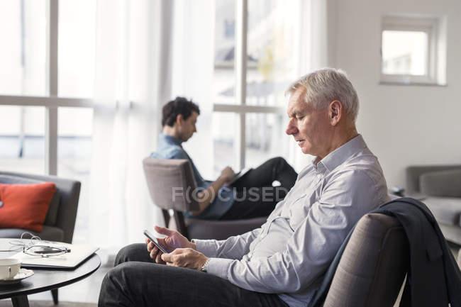 Uomini d'affari che utilizzano dispositivi nel ristorante — Foto stock