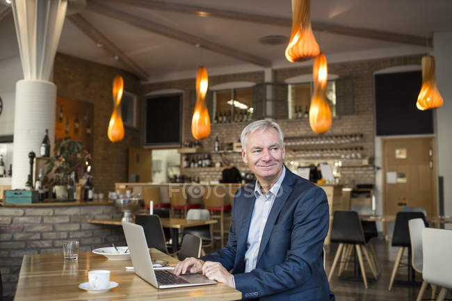 Smiling businessman using laptop — Stock Photo