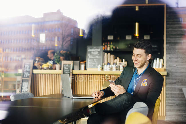 Hombre de negocios sonriente escuchando música - foto de stock