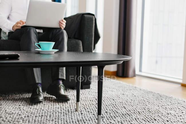 Empresario sentado con portátil - foto de stock